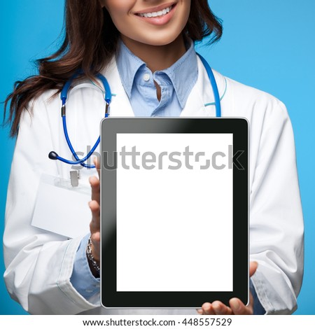 Portrait of happy smiling young female doctor showing blank tablet pc with copyspace area for slogan or text message, on blue background - stock photo