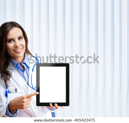 Portrait of happy smiling young female doctor showing no-name tablet pc with blank copyspace area for slogan or text, at office.  - stock photo