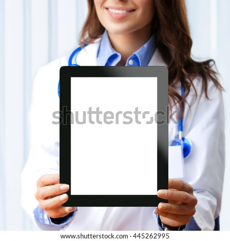 Portrait of happy smiling young female doctor showing no-name tablet pc with blank copyspace area for slogan or text, at office. Selective focus on tablet pc. - stock photo
