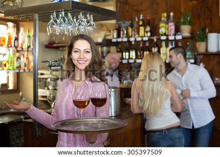 Portrait of happy smiling young girl working in modern bar as waitress