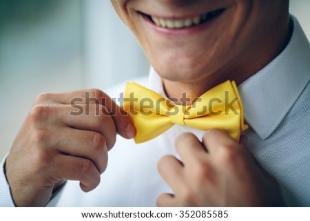 Portrait of happy smiling young man in a wedding costume and yellow butterfly tie over studio background. Closeup.Hands, lips, care, to correct, to adjust, fashion. - stock photo
