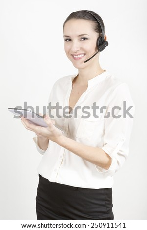 Portrait of happy smiling young support phone operator in headset at office with a tablet - stock photo