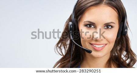 Portrait of happy smiling young support phone operator or businesswomen in headset, with blank copyspace area for slogan or text - stock photo