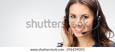 Portrait of happy smiling young support phone operator or businesswomen in headset, with blank copyspace area for slogan or text, posing at studio against grey background - stock photo