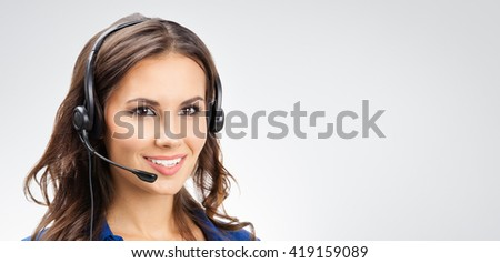 Portrait of happy smiling young support phone operator or businesswomen in headset, with blank copyspace area for slogan or text, against grey background - stock photo