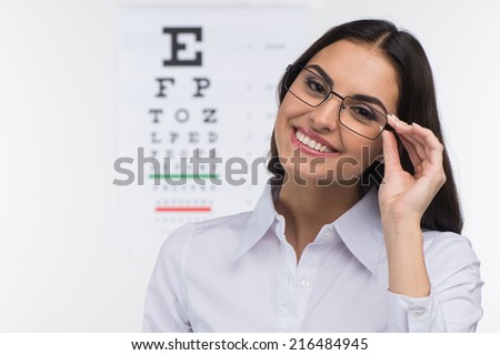 Portrait of happy smiling young woman. girl holding glasses in eye doctor, isolated over white background  - stock photo