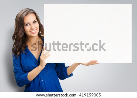 Portrait of happy smiling young woman in blue clothing, showing blank signboard with blank copyspace area for slogan or text, against grey background - stock photo