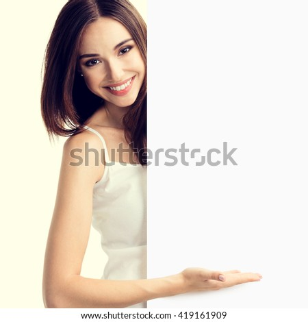 Portrait of happy smiling young woman in white tank top casual smart clothing, showing empty blank signboard with copyspace area for text or slogan - stock photo