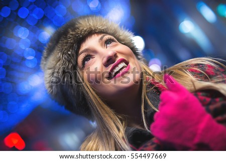 Portrait of happy smiling young woman, outdoor in night. New Year concept