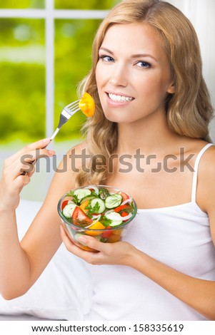 Portrait of happy smiling young woman with vegetarian vegetable salad, indoors