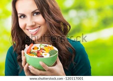 Portrait of happy smiling young woman with vegetarian vegetable salad, outdoors - stock photo