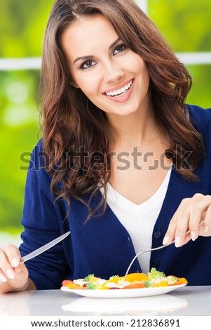 Portrait of happy smiling young woman with vegetarian vegetable salad, outdoors