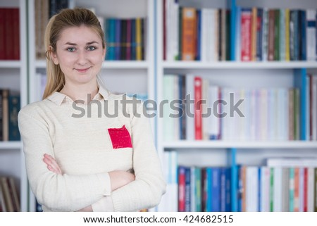 portrait of happy smilling female student girl in school library