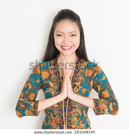 Portrait of happy Southeast Asian woman with batik dress in greeting gesture on plain background. - stock photo