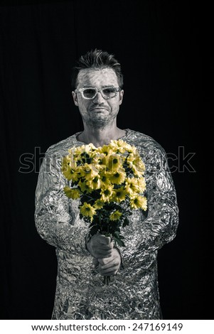 Portrait of happy spaceman holding flowers.