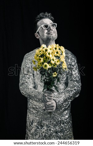 Portrait of happy spaceman holding flowers and looking up. - stock photo