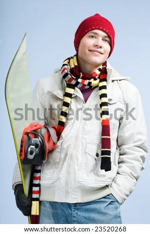 Portrait of happy sportsman with snowboard over blue background