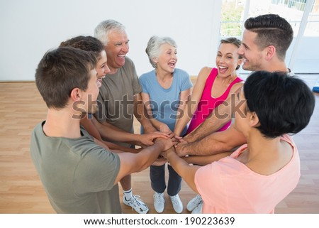 Portrait of happy sporty people holding hands together in the yoga class