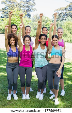 Portrait of happy sporty women clenching fist together at park - stock photo
