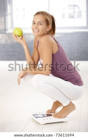 Portrait of happy squatter girl on scale holding green apple, laughing at camera.? - stock photo