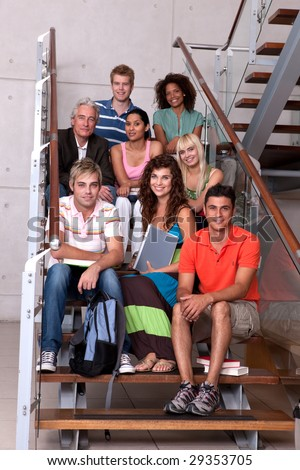 Portrait of happy student group sitting on staircase - stock photo