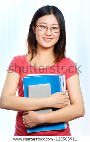 Portrait of happy student in eyeglasses holding books and looking at camera with smile - stock photo