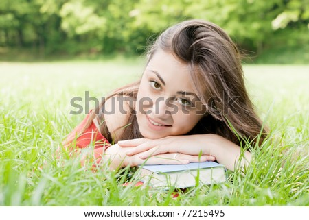 Portrait of happy student relaxed outdoors with book.