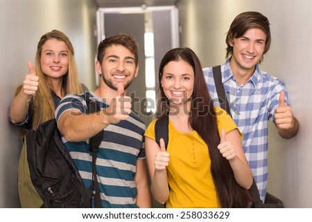 Portrait of happy students gesturing thumbs up at college corridor - stock photo