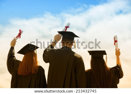 Portrait of happy students in graduation gowns holding diplomas on university campus - stock photo