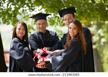 Portrait of happy students in graduation gowns holding diplomas on university campus