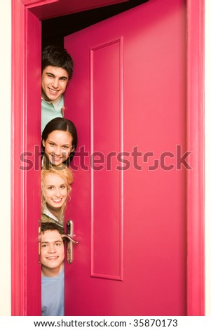 Portrait of happy students looking from behind door at camera with smiles - stock photo