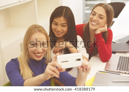 Portrait of happy students making selfies in library. Beautiful ladies posing for camera and smiling all together. Toned image.