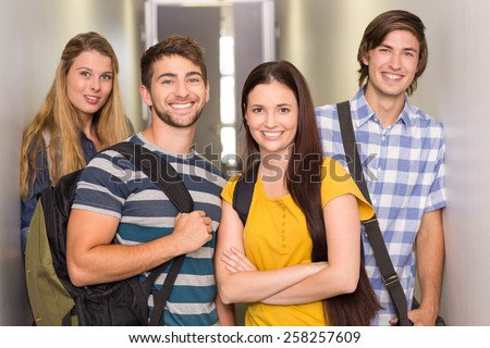Portrait of happy students standing at college corridor - stock photo
