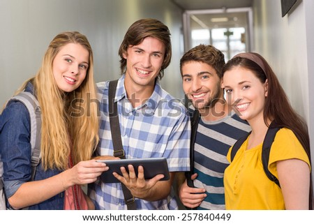 Portrait of happy students using digital tablet at college corridor - stock photo