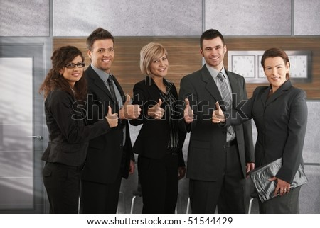 Portrait of happy successful business team showing thumbs up to camera in office. - stock photo