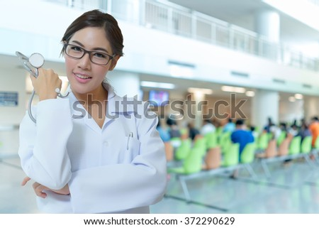 Portrait of happy successful young female doctor holding a stethoscope  - stock photo