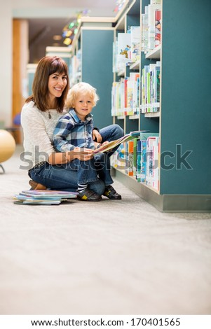 Portrait of happy teacher and boy reading book by bookshelf in library - stock photo