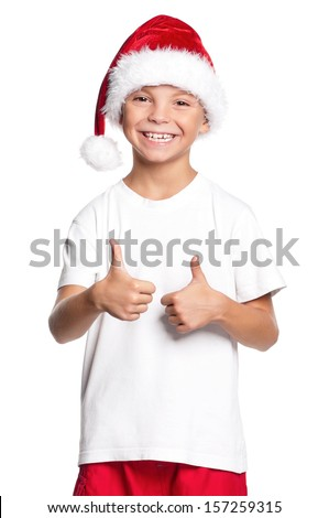 Portrait of happy teen boy in Santa hat with thumbs up isolated on white background - stock photo
