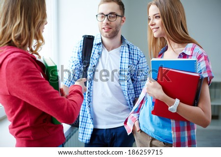 Portrait of happy teen friends talking during break in college - stock photo