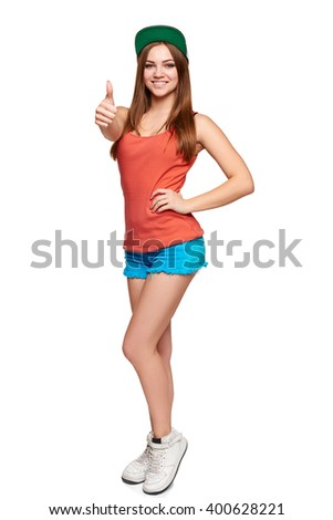 Portrait of happy teen funky girl in full length showing thumb up sign, over white background - stock photo
