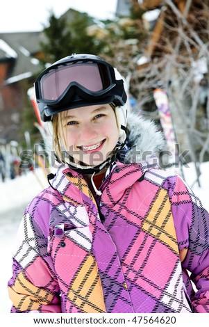 Portrait of happy teenage girl in ski helmet and goggles at winter resort - stock photo