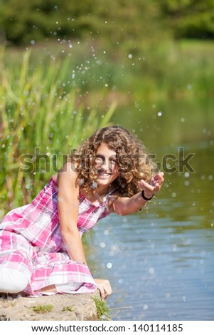 Portrait of happy teenage girl playing with water in park