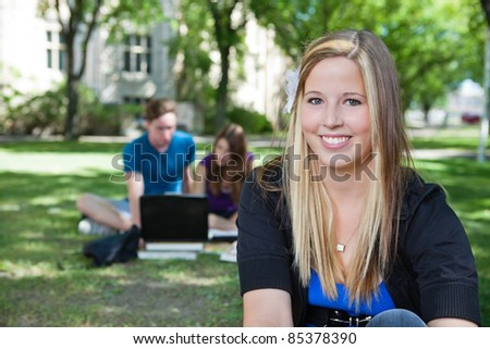 Portrait of happy teenage girl with classmates in background - stock photo