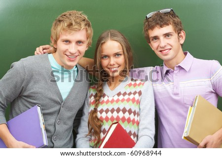 Portrait of happy teens by blackboard looking at camera with smiles - stock photo