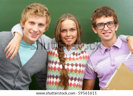 Portrait of happy teens embracing and looking at camera with smiles - stock photo