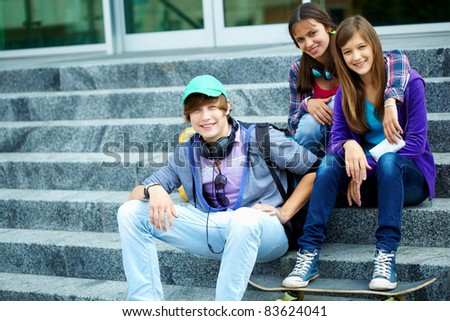 Portrait of happy teens on stairs looking at camera - stock photo