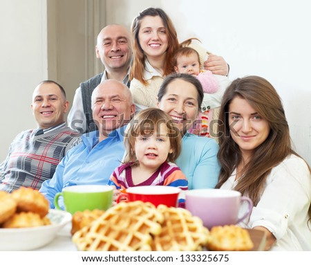 Portrait of happy three generations family posing together over tea at home - stock photo