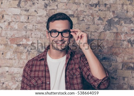 Portrait of happy toothy smart man touching his glasses