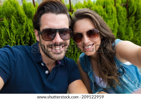 Portrait of happy tourist couple taking a selfie in the city. - stock photo
