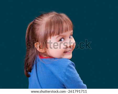 Portrait of happy turning around and smiling little girl on dark green background. Cheerful kid. - stock photo